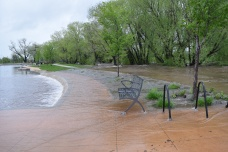 The water was spilling over the creek across the sidewalk and bench.